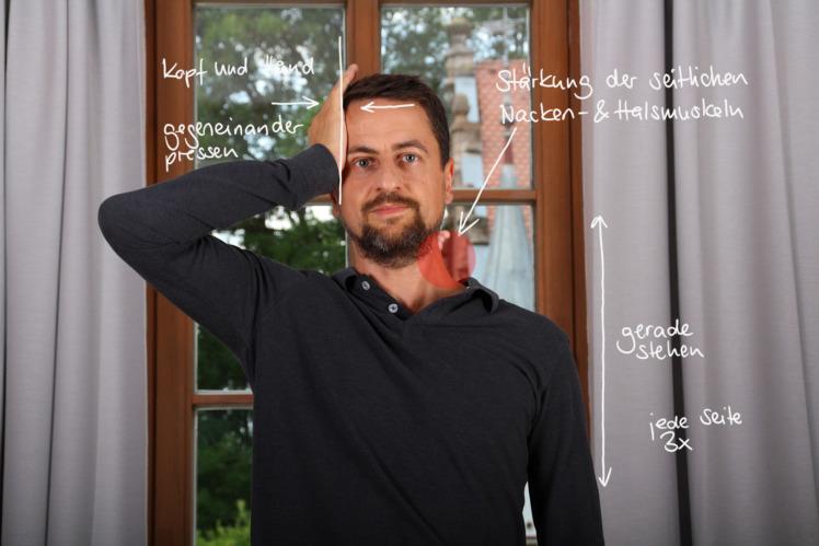 Stelle dich aufrecht hin und lege eine Hand an deine Schläfe, so wie du es in diesem Bild siehst. Dann drückst du mit dem Kopf für 3x 10 Sekunden gegen die Hand. Anschließend führst du die gleiche Übung auf der anderen Seite durch.