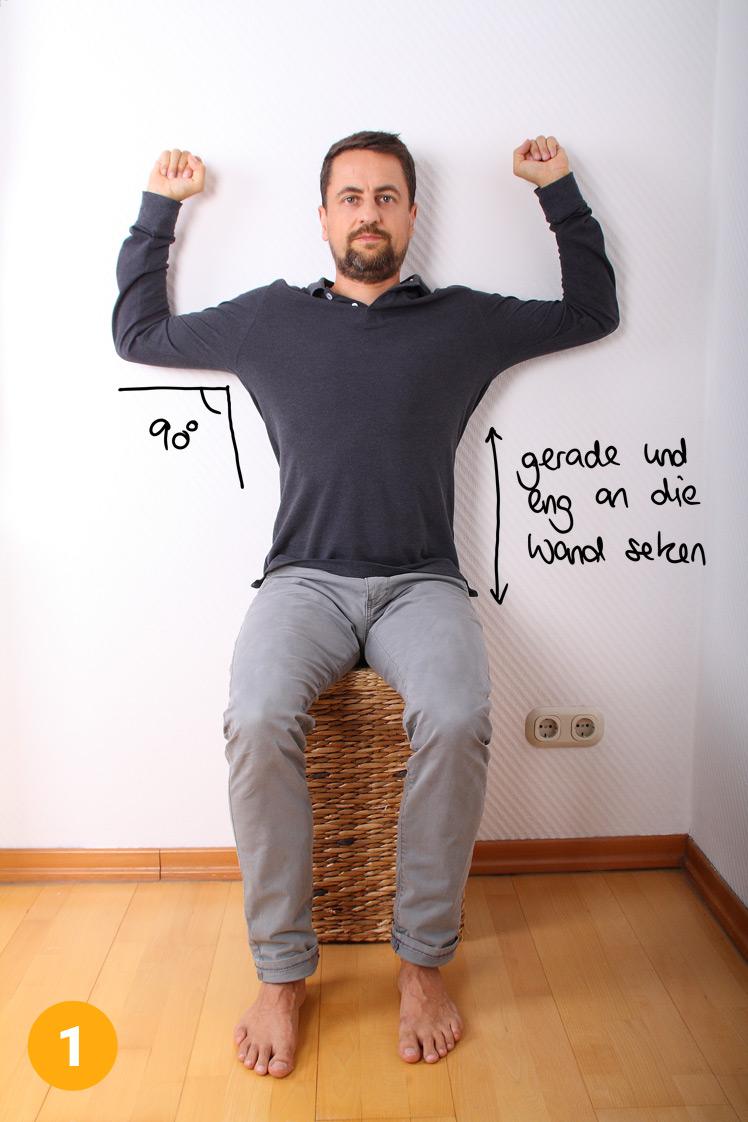 Setze dich mit einem Hocker oder Stuhl (Stuhllehne nach vorne) an die Wand. Der Po und der Rücken liegen exakt an der Wand an und verbleiben in dieser Position die komplett Übung über. Hebe deine Arme, so dass du einen 90° Winkel erreichst.