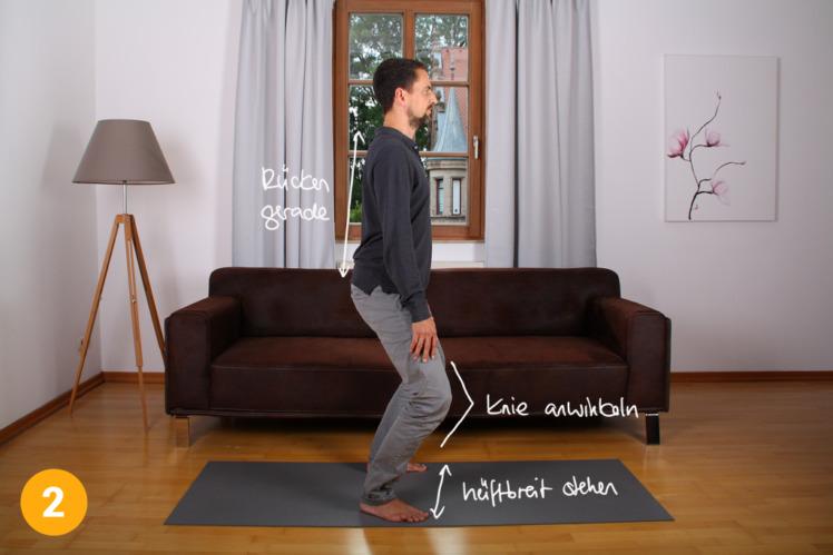 Gehe leicht in die Knie und bleibe in dieser Position die ganze Übung über. Die Füße stehen etwa 30 bis 40cm auseinander. Der Rücken bleibt gerade.
